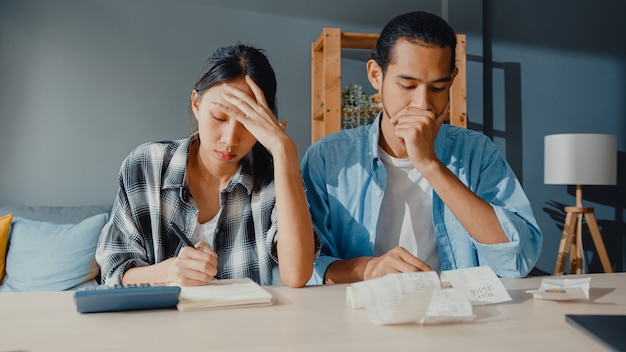 스트레스 아시아 부부 남자와 여자는 가족 예산을 계산하기 위해 계산기를 사용