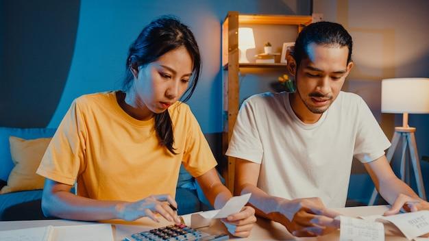 ストレスアジアのカップルの男性と女性は家族の予算を計算するために計算機を使用します