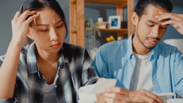 Stress asian couple man and woman use calculator for calculate family budget