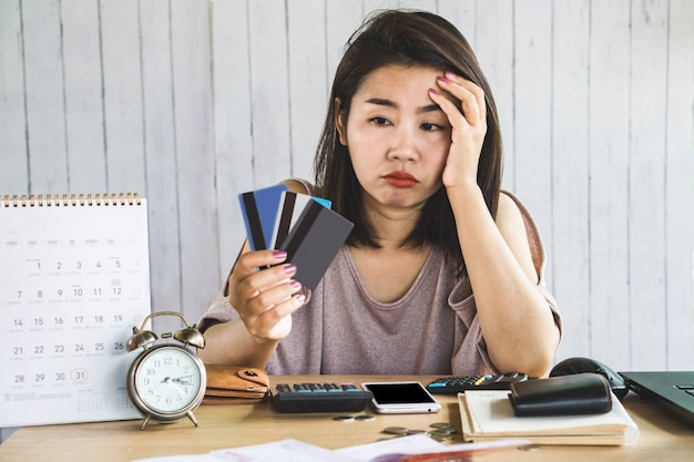 Stress asian woman looking at credit cards in hand
