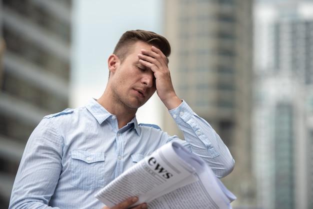 Стресс бизнесмен с газетой беспокоиться о новостях фондового рынка.