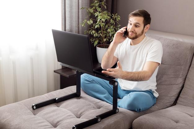 스트레스 백인 우울한 남자가 전화로 이야기하고 노트북과 인터넷을 사용하여 재택 근무