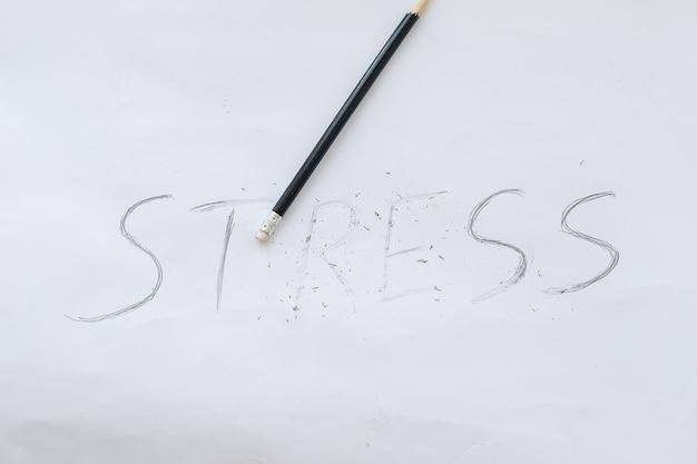 스트레스 개념입니다. 검은 부러진 연필로 흰 종이에 쓰여진 단어 스트레스.