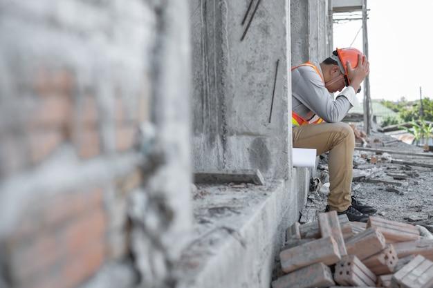 彼の頭で手を繋いでいるストレスエンジニアまたは建築家。彼は仕事に問題を抱えています。エンジニアリングの概念。