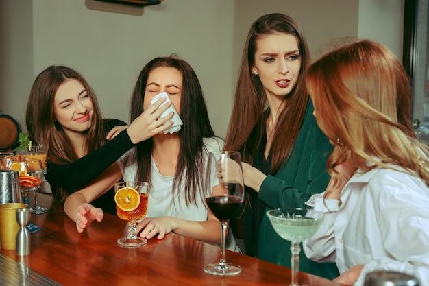 스트레스. 술집에서 술을 마시고있는 여자 친구. 그들은 칵테일과 함께 나무 테이블에 앉아 있습니다. 그들은 평상복을 입고 있습니다. 우는 소녀를 위로하고 달래주는 친구