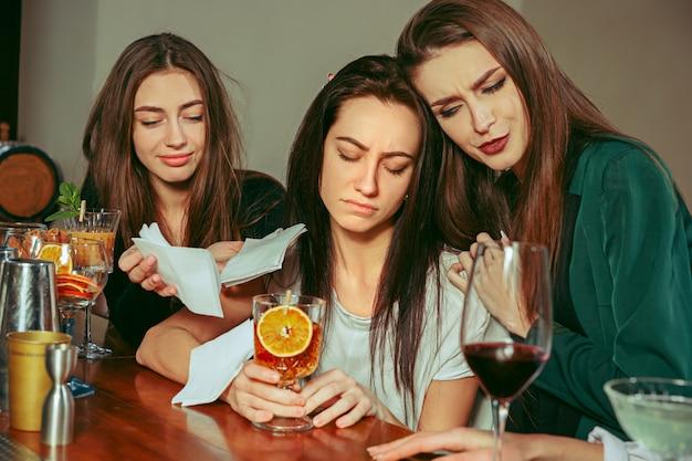 ストレス。バーで飲み物を飲んでいる女性の友人。彼らはカクテルを片手に木製のテーブルに座っています。