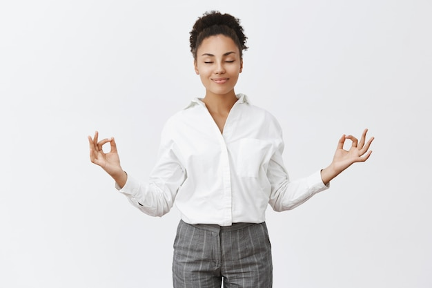Без стресса, только мир внутри. очаровательная расслабленная и беззаботная женщина в строгом наряде, поднимающая руки в жесте дзен, улыбающаяся с закрытыми глазами во время медитации или занятий йогой, чувствуя облегчение