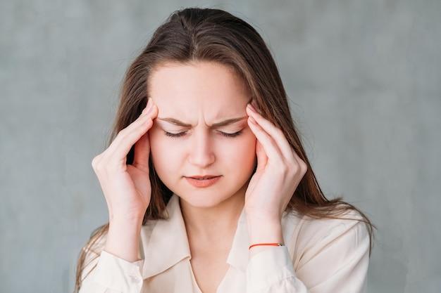 ストレスの頭痛。寺院に触れる疲れた女性。美しい若い女性の肖像画。
