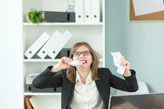 ストレスオフィスと人々は、オフィスのテーブルに座って多くの仕事をしている女性労働者を概念化します