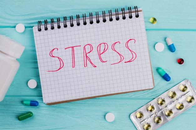 파란색 책상에 있는 메모장과 다양한 약물에 대한 스트레스. 약간의 물집 팩.