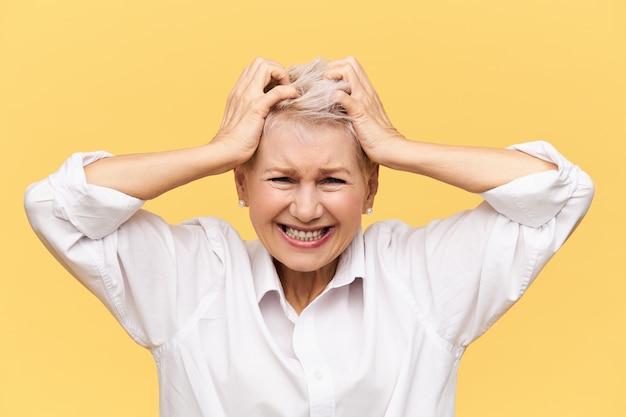 ストレス、問題、怒り、怒り、否定的な感情。欲求不満の絶望的な成熟した女性は、失敗で怒っている髪を叫び、引き裂き、経済的な問題でストレスを感じ、彼女の気性を失います