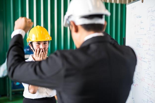 스트레스 슬픈 공장 여성 노동자는 제조 계획 지연에 대해 상사의 비난과 소리를 지릅니다.