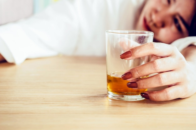 Stress woman hand drinking glass of alcohol