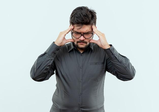 Stress giovane imprenditore indossando occhiali mettendo la mano sulla fronte isolato su bianco