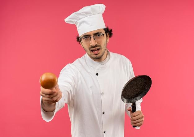Stress giovane cuoco maschio indossa uniforme da chef e bicchieri tenendo padella con cucchiaio