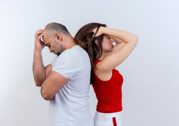 Sottolineato coppia adulta in piedi schiena contro schiena sia mettendo la mano sulla testa isolata sulla parete bianca con lo spazio della copia