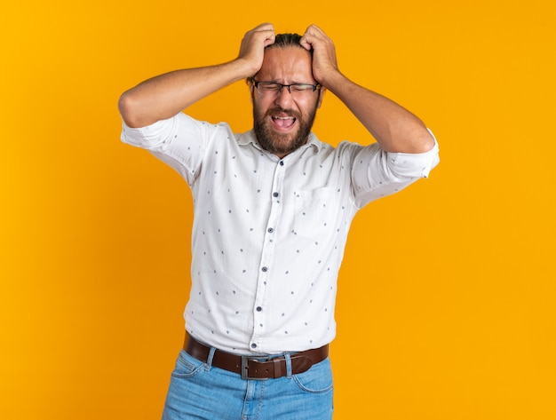 Stressed adult handsome man wearing glasses keeping hands on head screaming with closed eyes