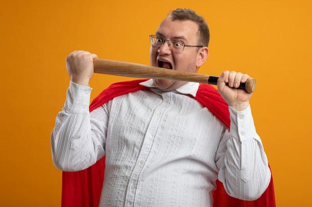 オレンジ色の壁にまっすぐに孤立してそれを噛む準備をしている口の近くに野球のバットを保持している眼鏡をかけている赤い岬の強調された大人のスラブのスーパーヒーローの男