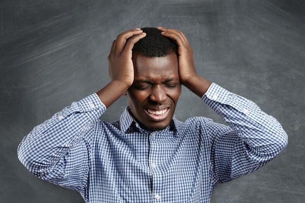 ひどい頭痛、頭を圧迫し、目を閉じ、痛みを伴う欲求不満な表情で歯を食いしばったアフリカのビジネスマンを強調しました。片頭痛に苦しんでいる苦痛の浅黒い肌の起業家