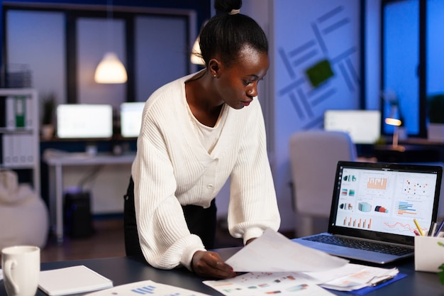 Stressed african manager woman working with financial documents checking graphs, holding papers, reading raports, standing at desk late at night in start-up office doing overtime to respect deadline
