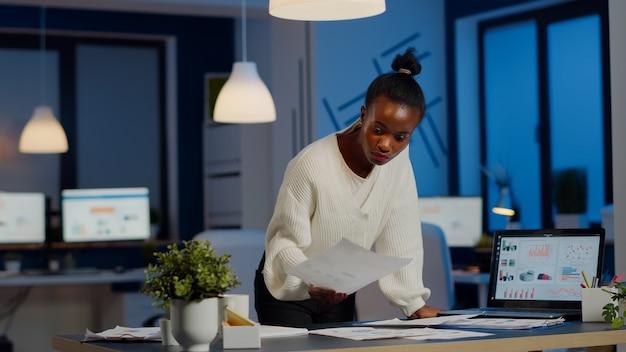デスクに立ってグラフをチェックし、書類を持って、締め切りを守るために残業をしているスタートアップオフィスで夜遅くに報告書を読んでいる財務書類を扱うアフリカのマネージャーの女性を強調しました。