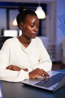Stressed african manager woman working with financial graphs checking statistics, typing on laptop, reading raports late at night in start-up office doing overtime to respect deadline of project