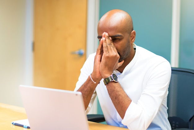 Stressed afro american businessman in the office with his laptop