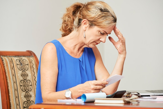 Stressed almost crying middle-aged woman reading payment request document or eviction notice