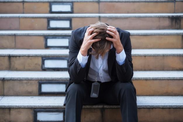 스트레스를 받는 미국 사업가는 covid-19 또는 코로나 바이러스 델타의 영향으로 해고되거나 해고된 후 계단에서 머리를 숙입니다. 무급 회사 휴가, 재택 근무 또는 실업.