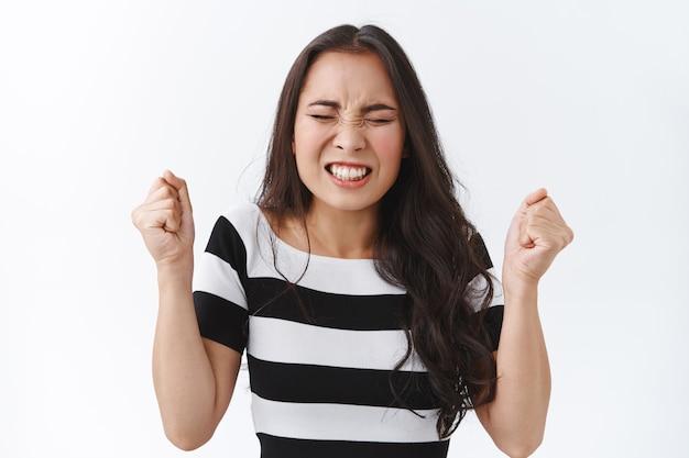 ストレスと不安の若いパニック状態の若いアジアのブルネットの女性が縞模様のtシャツを着て、握りこぶしを上げ、目を閉じて歯を食いしばって神経質に振って、苦しんで圧力をかけている