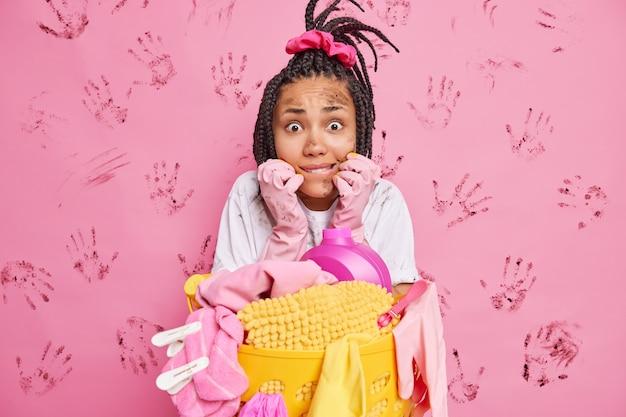 Напряженная и нервная молодая афроамериканка с грязным лицом кусает губы на розовой стене с отпечатками ладоней