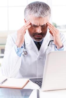 스트레스 받고 피곤한 의사. 직장에 앉아 있는 동안 손으로 머리를 만지는 우울한 성숙한 회색 머리 의사