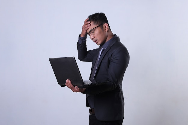 Stressed asian businessman holding a laptop