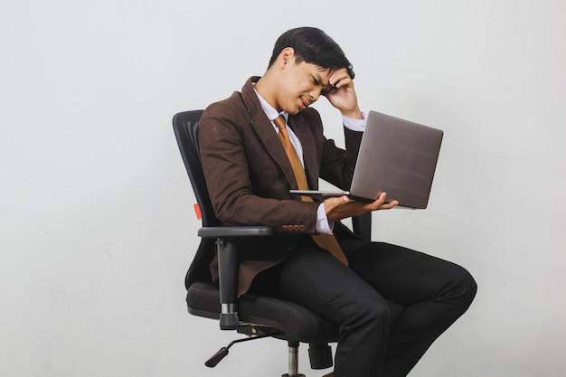 Подчеркнул азиатский бизнесмен в пиджаке и галстуке сидит, глядя на ноутбук