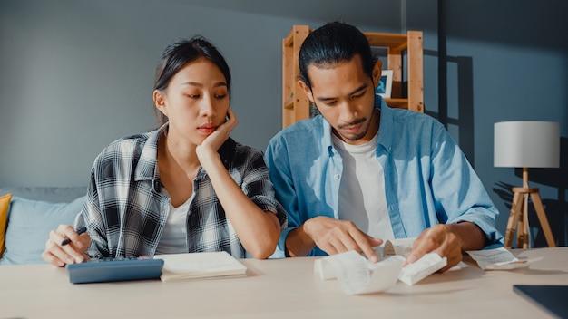 強調されたアジアのカップルの男性と女性は家族の予算を計算するために計算機を使用します