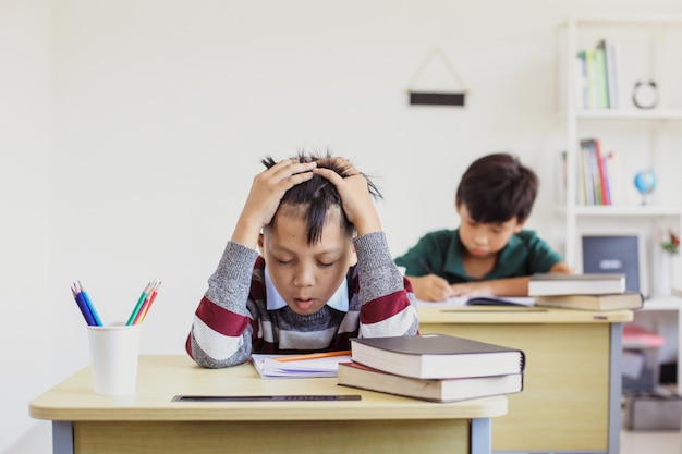 Stressed asian student during exam in the classroom