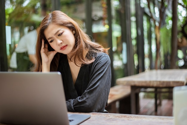 Stressed asian woman feeling headache in cafe shop