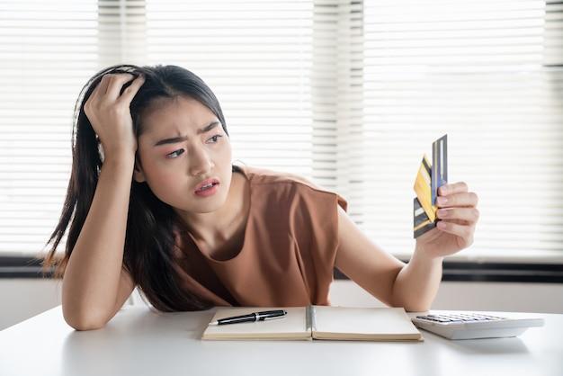 신용 카드를 들고 있는 아시아 여성은 빚을 갚을 돈이 없다고 강조했습니다. 재정 문제 개념