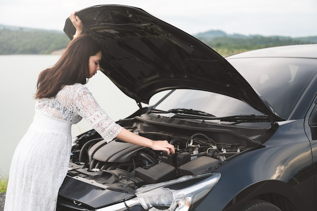 Stressed asian woman open hood, looking a broken car and checking engine on country road.