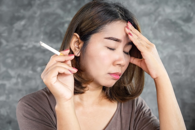 Stressed asian woman smoking cigarette over thinking