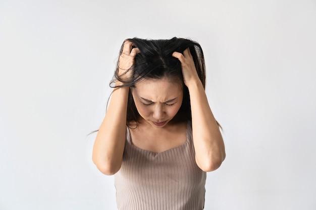 うつ病に苦しんでいるアジアの女性を強調した。女性は片頭痛と頭痛に苦しんでいます。コピースペース