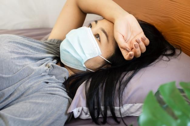 ベッドで考えすぎているフェイスマスクでアジアの女性を強調