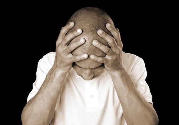 Stressed bald man on black background
