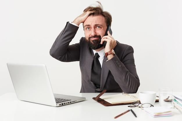 ストレスのたまったひげを生やしたブルネットの男性が作業テーブルに座って緊張した電話で会話し、混乱した顔で髪をしわくちゃにし、灰色のスーツを着て困惑しているように見えます