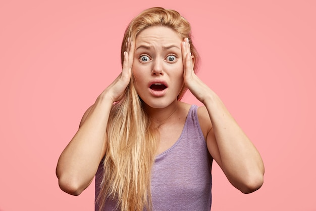 Подчеркнутая красивая блондинка держит руки на висках, с испуганным выражением лица, в панике, когда слышит ужасные новости, широко открывает рот, одетая в фиолетовую футболку, стоит в одиночестве у розовой стены