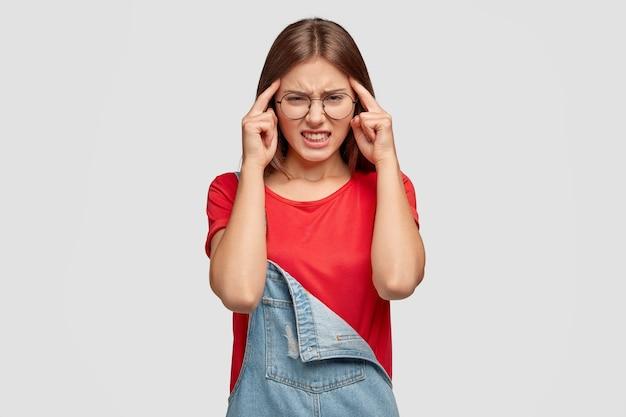 Подчеркнутая красивая женщина держит пальцы на висках, недовольно щурит лицо, страдает мигренью, пытается сосредоточиться или сосредоточиться