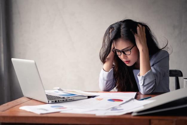 ノートパソコンを使用して仕事をしているストレスの多いビジネスアジアの女性