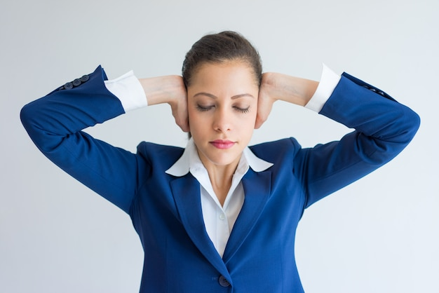 Stressed business woman covering ears with hands and closing eyes.