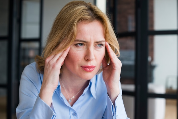 Stressed business woman holding head
