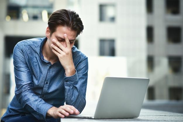 Подчеркнул бизнесмен после провала проекта. сбитый с толку молодой человек разочарован интернет-проблемой.